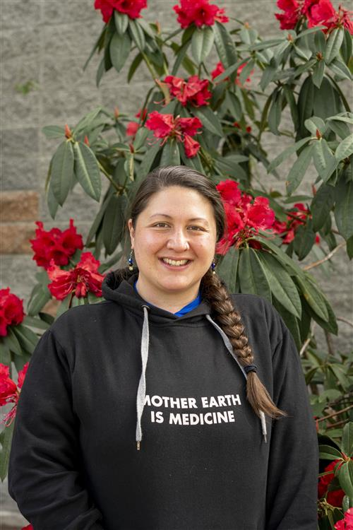 Adrienne Nichols stands with a black sweatshirt on with red flowers behind her.