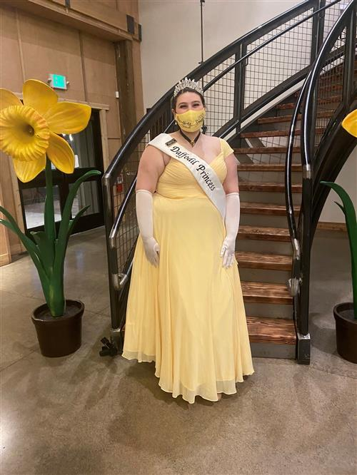 Szoi Stevens in long yellow dress with white sash that says in black letters Daffodil Princess